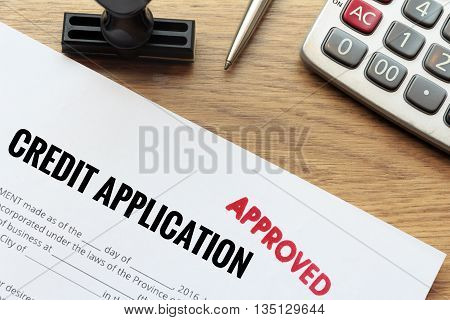 Approved credit application form lay down on wooden desk with rubber stamp and calculator.
