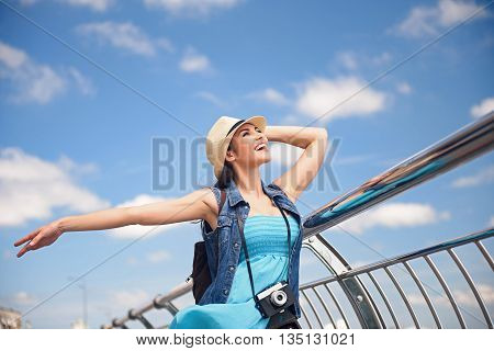 I am free. Pretty young woman is enjoying scenery. She is looking at sky and smiling. Tourist is standing and relaxing