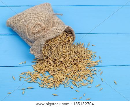 Canvas bag with grains oats on wooden table