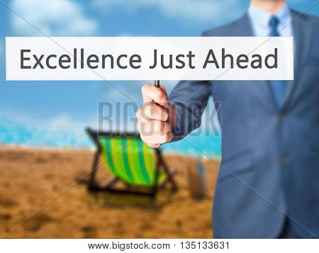 Excellence Just Ahead - Businessman Hand Holding Sign