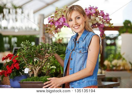 Smiling woman with an apple tree bonsai in a nursery