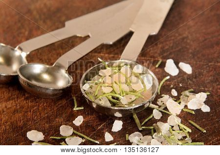 dried rosemary with coarse sea salt on a measurement spoon