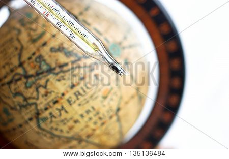 broken thermometer with vintage globe background a sign of global warning
