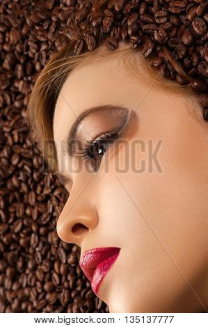 beautiful profile face in coffee beans closeup