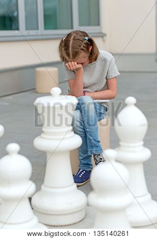 Little girl playing outdoor the chess game.