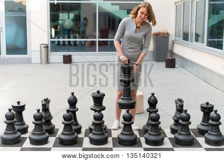 Young woman playing outdoor the chess game.