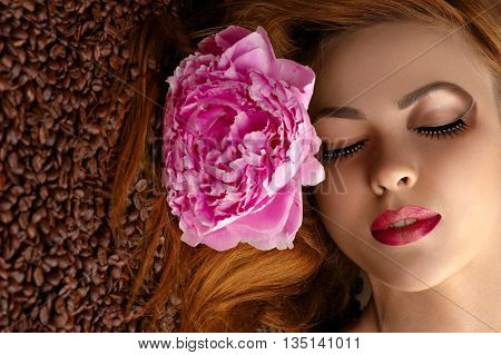 beautiful woman face with peony on coffee beans