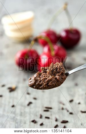 spoon with chocolate mousse on rustic wood