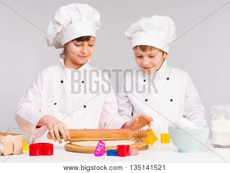 two little cooks in white uniform rolling out a dough in the kitchen