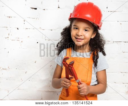 smiling little girl-worker in uniform and helmet with pliers in hands