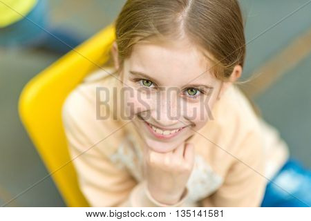 portrait of beautiful little girl with freckles looking at camera