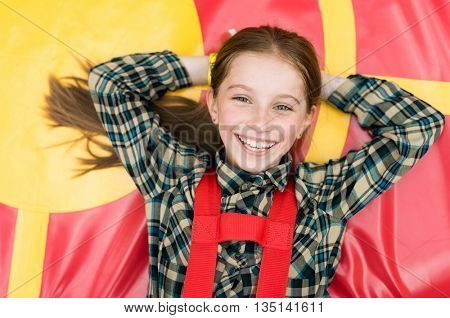 smiling joyful girl lying on colorful trampoline in entertainment center