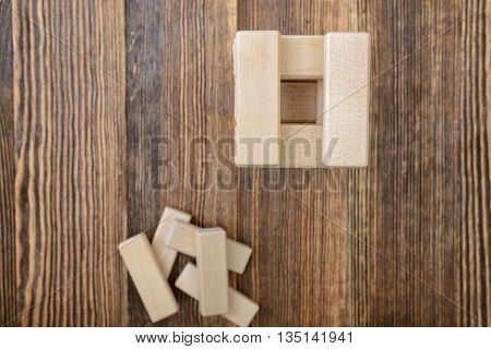 Top view of the tower of wooden blocks placed on a table. Removing blocks from a tower. Keeping balance. Full concentration. Entertainment activity. Game of physical and mental skill. Close-up photo.