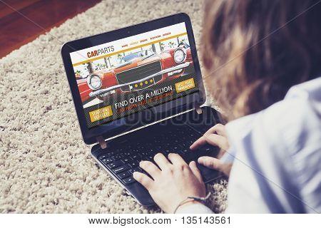 Car parts search. Auto repair shop website in a laptop computer. Woman navigating web.