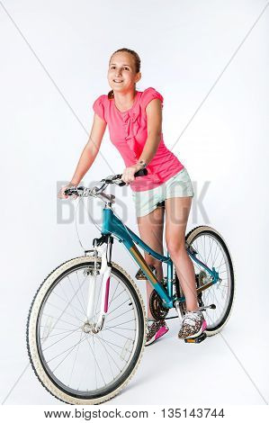 Teenager schoolgirl sitting next to his bicycle