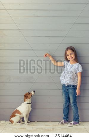 Cute little daughter is smiling and looking at camera while playing with her dog