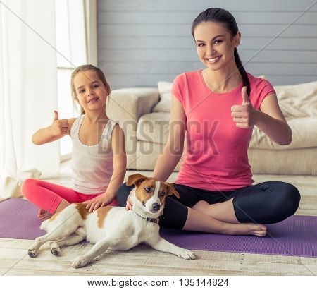 Beautiful young mother and her cute little daughter are showing Ok sign and smiling while sitting in with their dog on yoga mat at home
