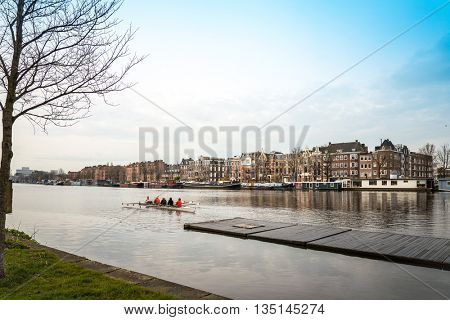 Amsterdam, Netherlands - March 31, 2016 : Beautiful view of Amsterdam canals with bridge and typical dutch houses. Amsterdam, Netherlands