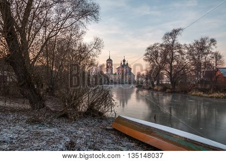 Landscape with the boat, the first ice on the river and reflection of orthodox church