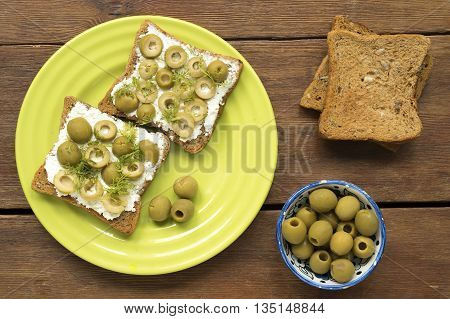 fried square toasts with soft cheese and green olives on the wooden table top