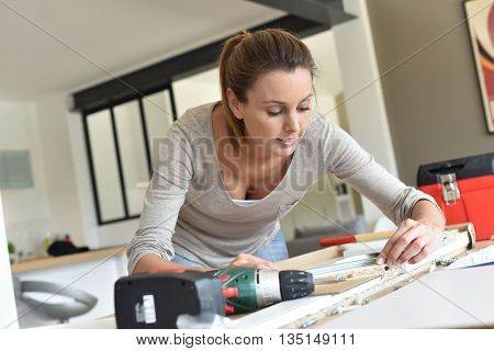 Woman at home assembling new furniture