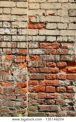 texture of old dilapidated shabby brickwork of red brick wall foreground closeup