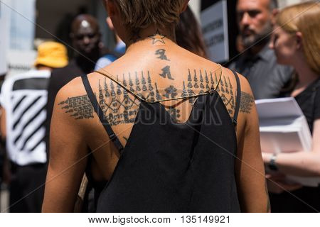 MILAN ITALY - JUNE 18: Detail of a fashionable woman with tattoos outside Marni fashion show building for Milan Men's Fashion Week on JUNE 18 2016 in Milan.