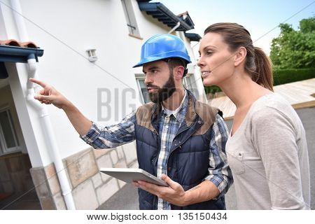 Technician with client showing what is being fixed