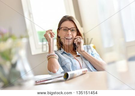 Trendy home office businesswoman talking on phone