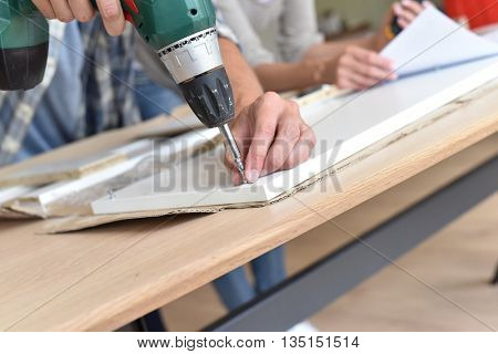 Closeup of electric drill assembling furniture pieces