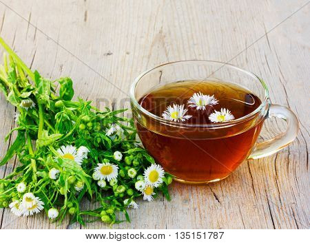 a nice cup of tea with camomile flowers and camomile on an old wooden table in the cracks close up