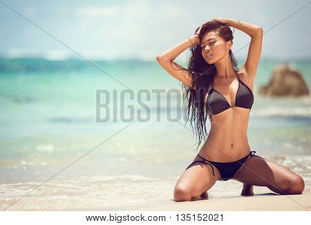 Attractive girl sensual posing on sandy beach