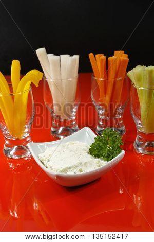 Healthy snacks - colorful vegetable sticks and yogurt dip
