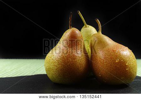 Fresh ripe organic green pears on green and black background