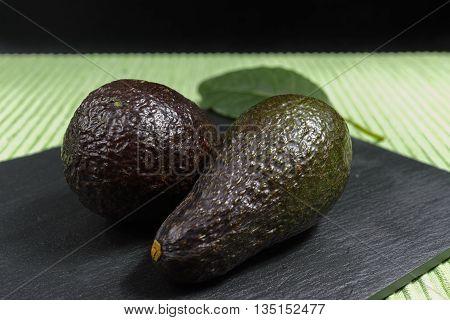 Fresh ripe organic green avocado on green and black background