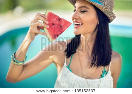 Young woman with summer hat bites juicy watermelon