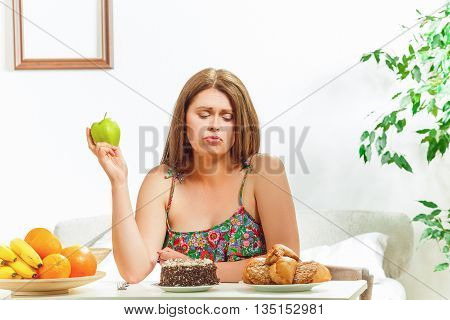 Diet concept. Pretty fat woman on diet sitting at table full of healthy and unhealthy dishes at home. Lady thinking whether to eat it or not.