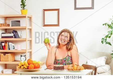 Beautiful fat woman on diet sitting at table and holding green apple at home. Toothy smiling woman looking away.