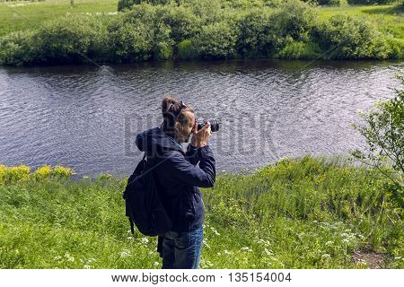 guy with backpack and dark glasses stands back and takes pictures of field on the camera