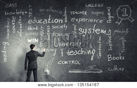 Rear view of man drawing education concept on blackboard with chalk