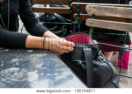 Female hands searching through a purse. Looking for keys.