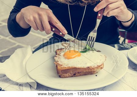 Attractive woman enjoying sunny side up egg on french toast. Breakfast in the city.