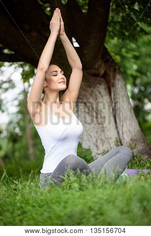 Relaxed young woman is meditating in park. She is sitting on grass and stretching arms up. Her eyes are closed with pleasure