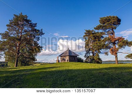 Pushkinskiye Gory, Russia - June 5 : Wooden chapel and stone cross on the top of Savkin hill, Pushkinskiye Gory Reserve, Russia . Birthday of the great writer Alexander Pushkin , on June 5, 2016.