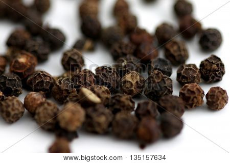 Group of black pepper corns on white background.