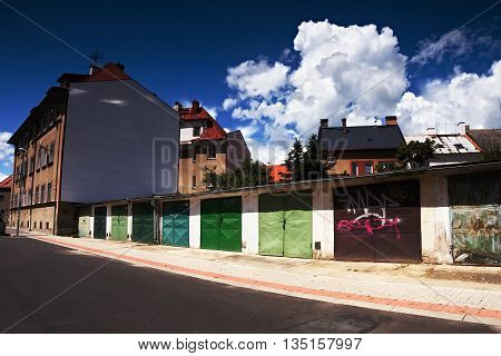 2016/06/18 - Chomutov city, Czech republic - nice dark blue sky with large white clouds above the houses with garages in the Roosevelt street in Chomutov city in Czech republic