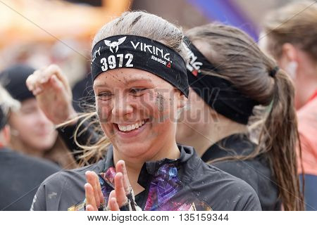 STOCKHOLM SWEDEN - MAY 14 2016: Smiling happy woman with mud in her face clapping hands after finishing the obstacle race Tough Viking Event in Sweden May 14 2016