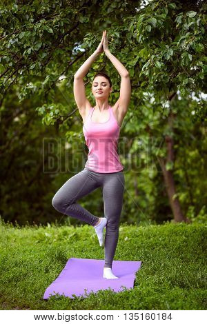 Calm young woman is doing yoga in park. She is standing on one leg and stretching arms up