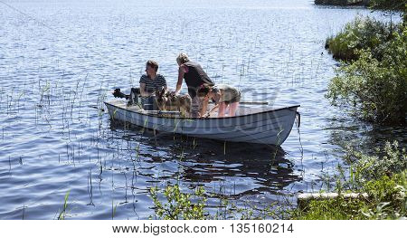 LAPLAND, SWEDEN ON JUNE 06. View of people set out in a small boat on June 06, 2013 in Lapland, Sweden. Warm day, lots of mosquitoes ashore. Unidentified persons. Editorial use.