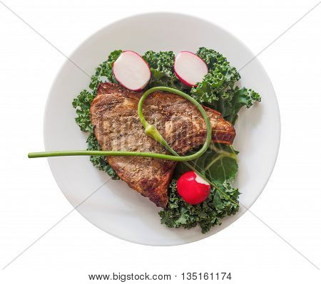Pork chop with garlic scapes on a plate, isolated on white